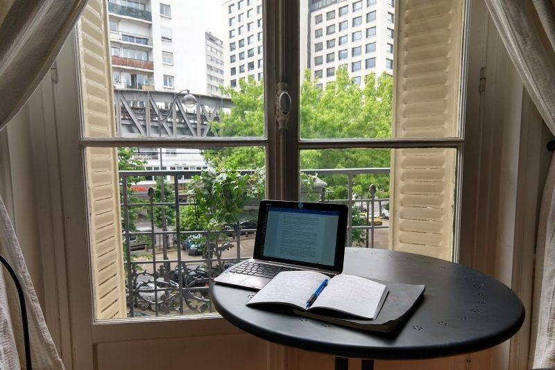 working on laptop next to a window in paris